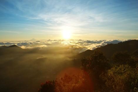 Dewi sangat menikmati sunrise dari puncak gunung